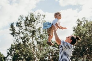 mom in striped shirt lifting blonde son into air in front of trees