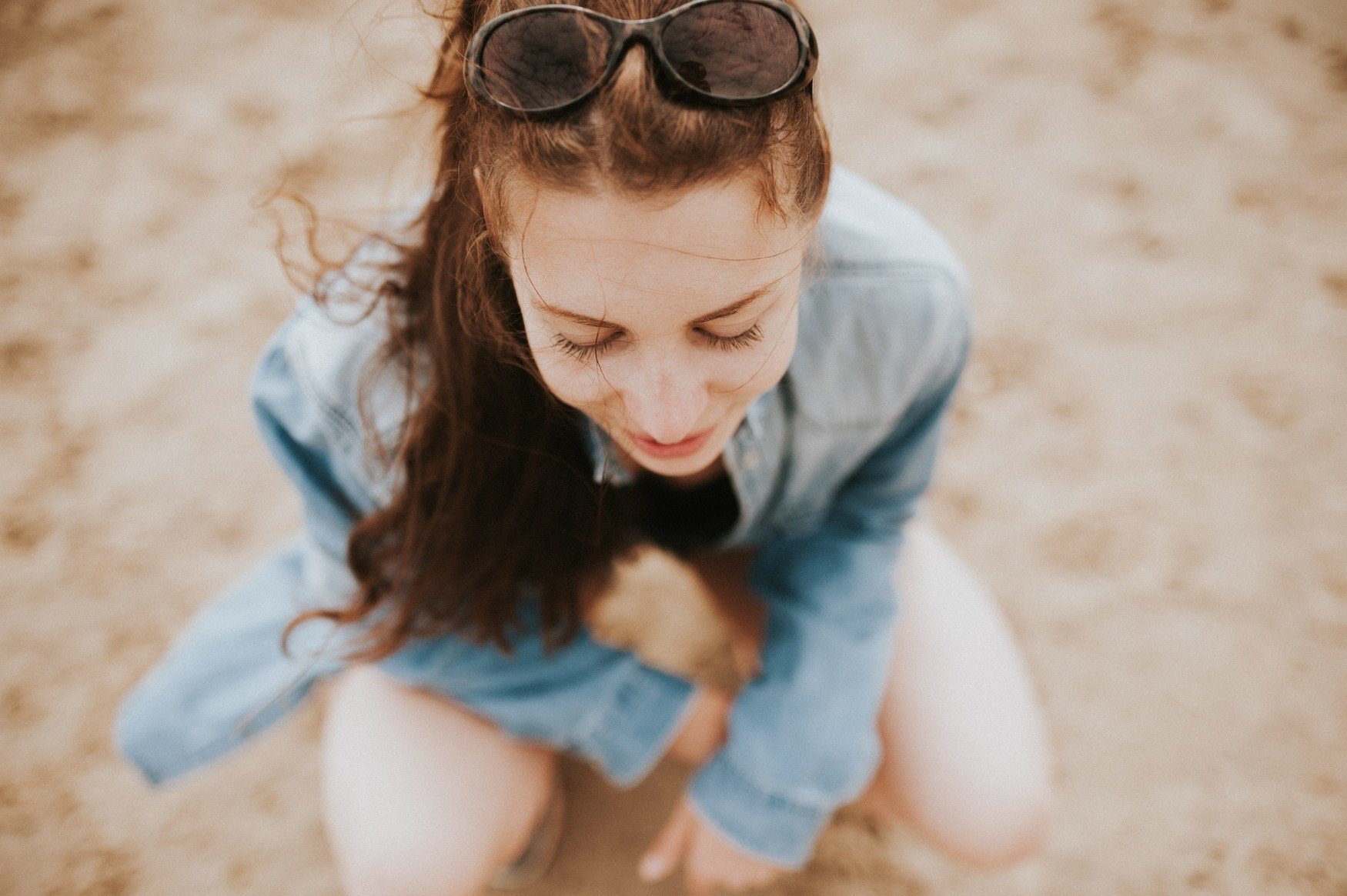 redhead woman crouching looking peaceful in jean jacket